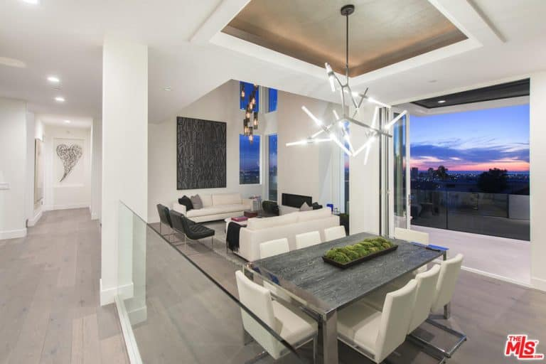 This view of the dining and living space showcases the beautiful white walls and classy flooring along with glass windows overlooking the Los Angeles city.