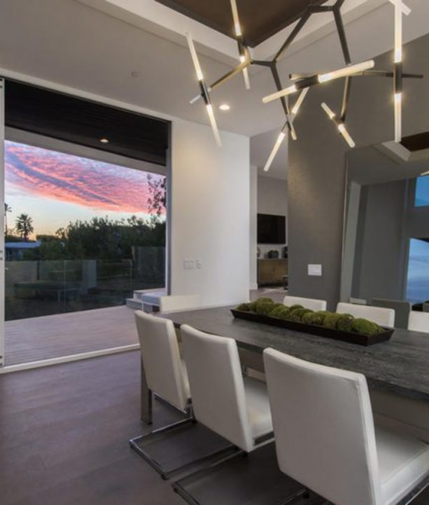 The dining room features modish table and chairs set lighted by a stylish ceiling light.