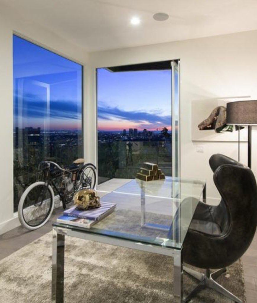 The home also features a home office with a black stylish wall and a floor to ceiling windows overlooking the city of Los Angeles.