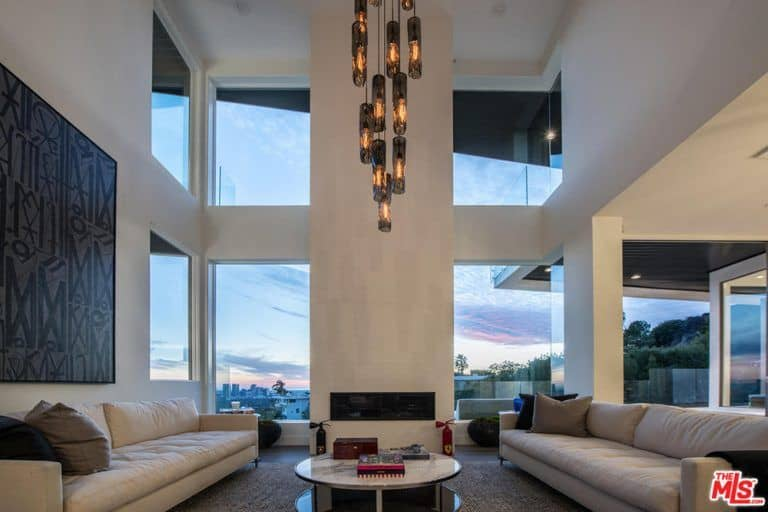 The living room features a towering high ceiling and a grand chandelier along with modish furniture and wall decor.