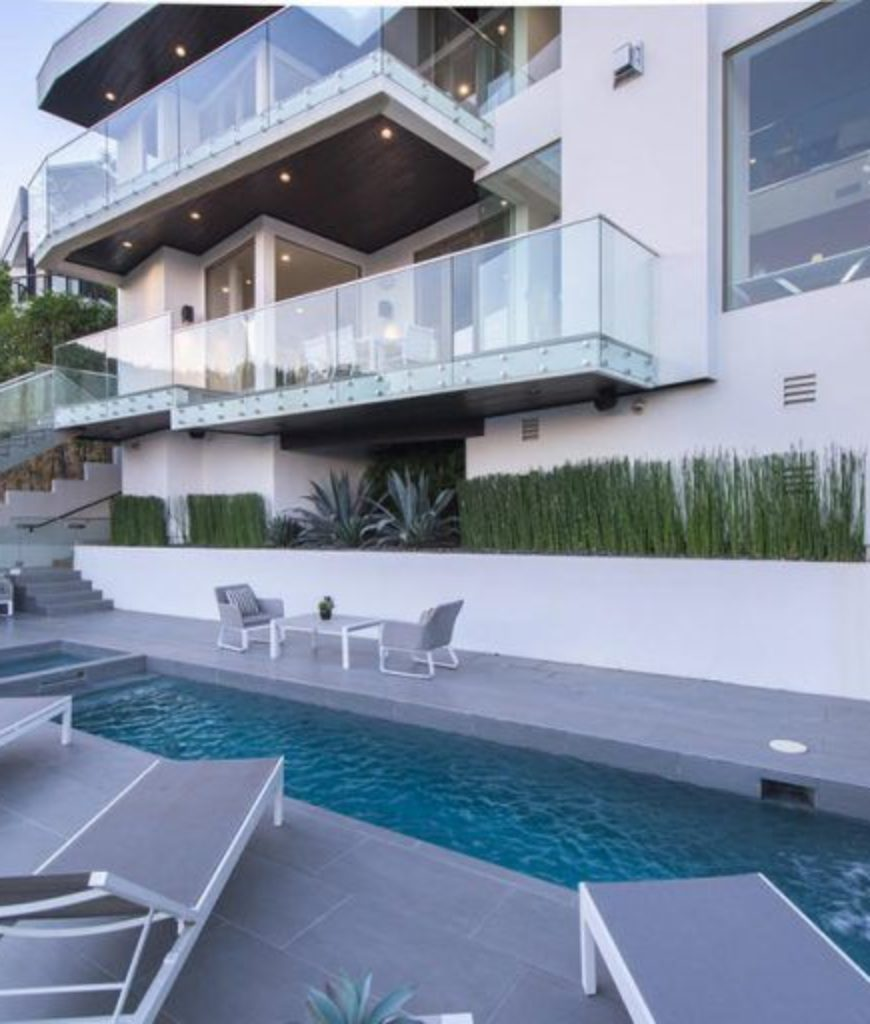 Another view of the swimming pool featuring the stylish pool, multiple lounges and beautiful house's architecture design.