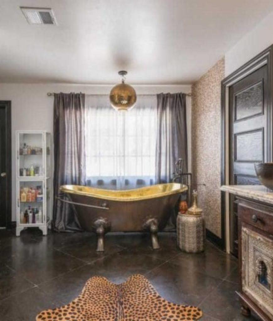 The bathroom has an elegant-looking bathtub, shower room and classy sink.