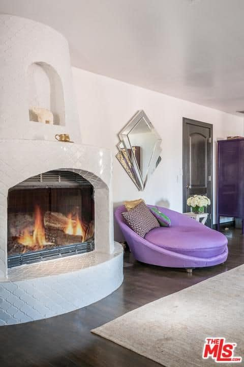 Close up view at the primary bedroom's fireplace and purple seat.