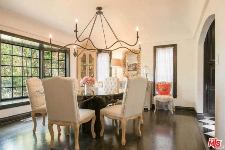 The dining room looks elegant with its table and chairs set and chandelier.