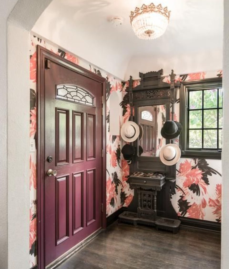 The entry features hardwood flooring, colorful-designed walls and flushmount light.