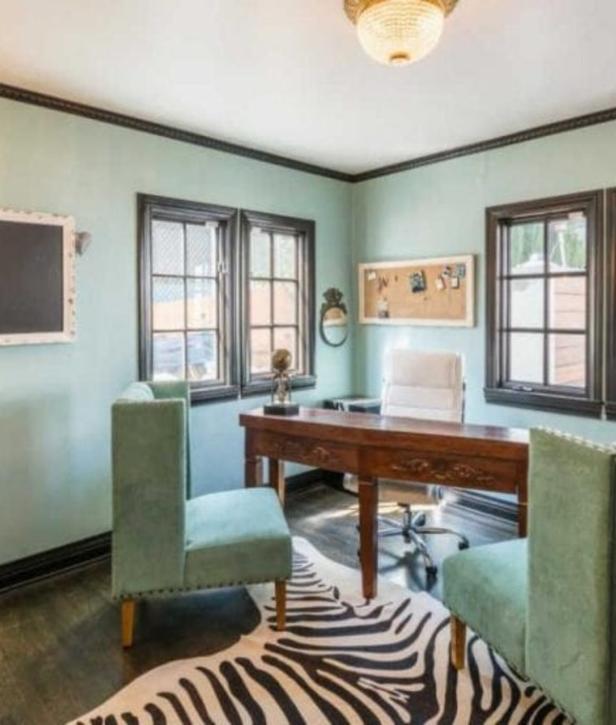 The home office features green walls and seats along with a hardwood flooring and a stylish rug.