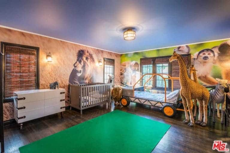The kids bedroom features a hardwood with a green rug along with a very child-friendly theme.