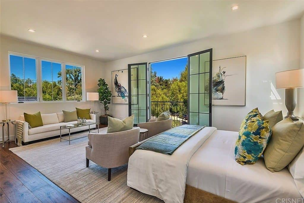 Spacious master bedroom with hardwood floor, sofa, two armchairs and double glass doors leading to a patio.