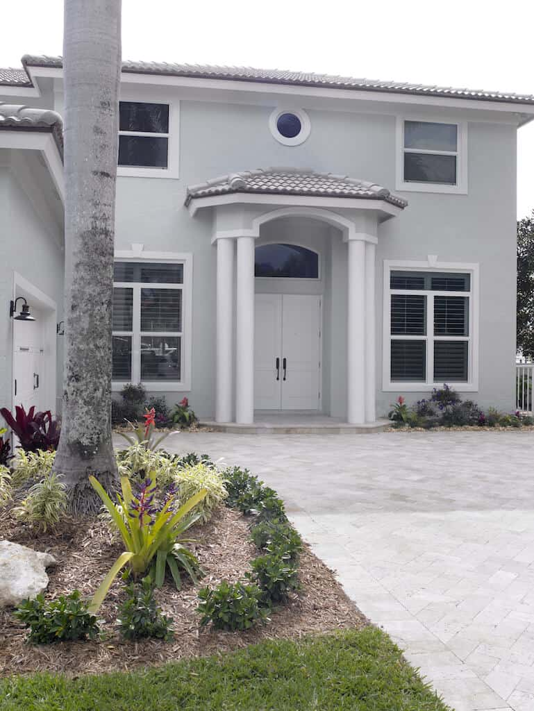 This coastal contemporary house features a gray exterior and a nice small garden area.