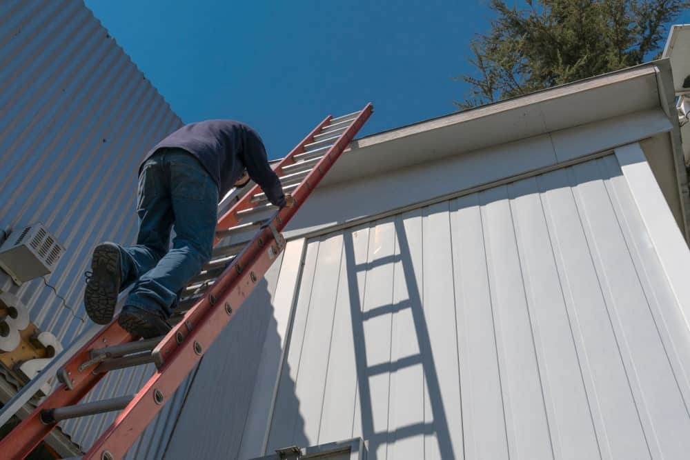 Man climbing up a ladder to reach the top of the house.