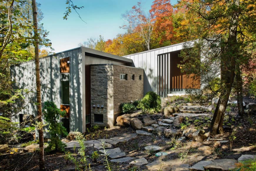 This cottage house is surrounded by beautiful nature. It also has a nice walkway and a gray exterior.