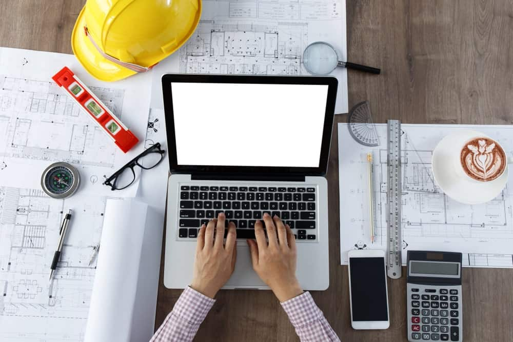 An architect types on the laptop surrounded by architect tools on a wooden desk.