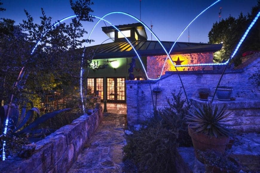 This is a front view of the house with large glass doors and stone exterior walls and walkways. These are then complemented by the colorful outdoor lighting.