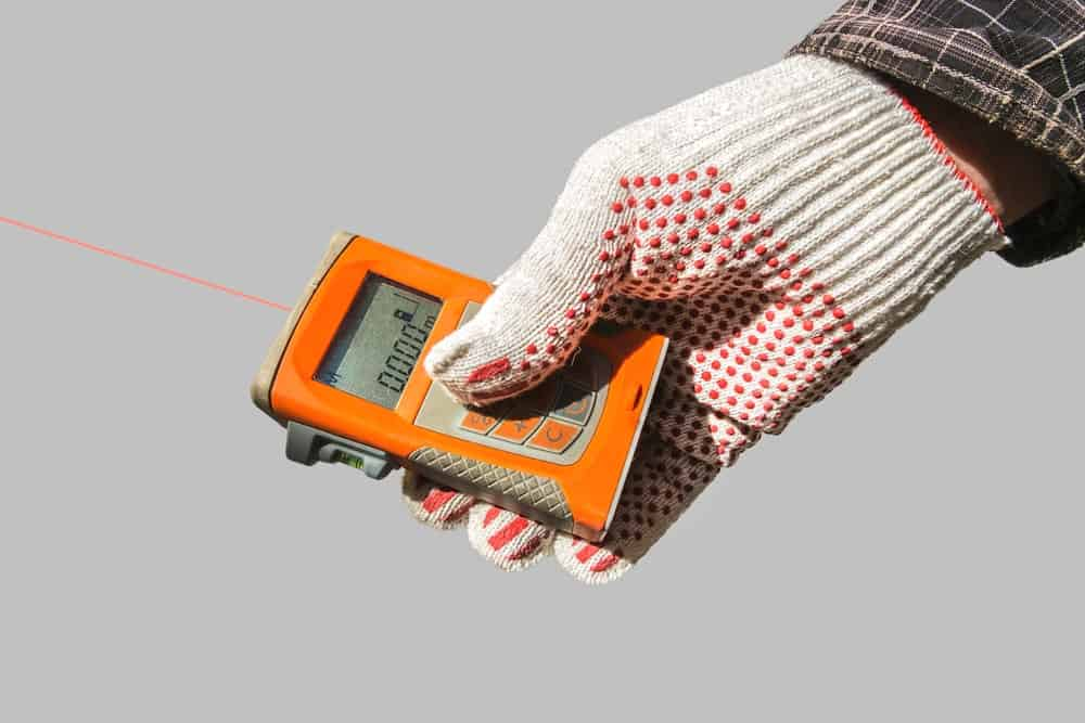 Hand holding a laser distance measuring tool.