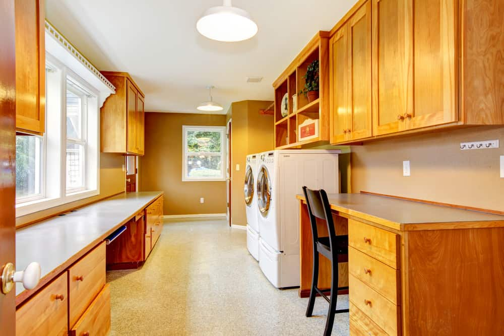 Huge long laundry room with built-in desk, long counter and plenty of cabinets on vinyl floor.