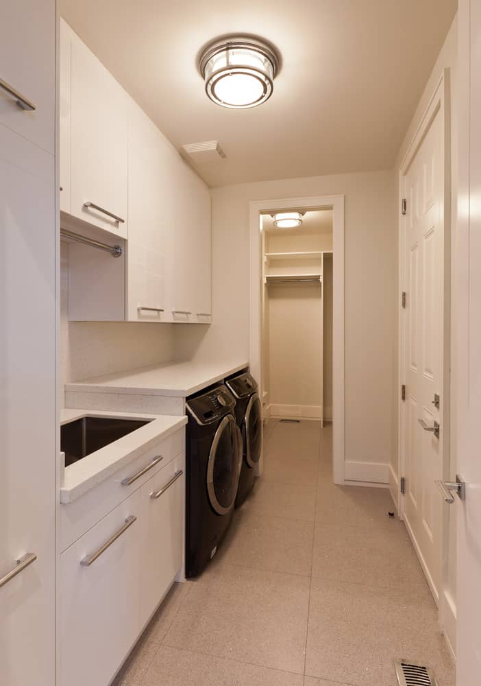 All white narrow, long laundry room with plenty of storage space and a long rectangle sink next to the washing machine.