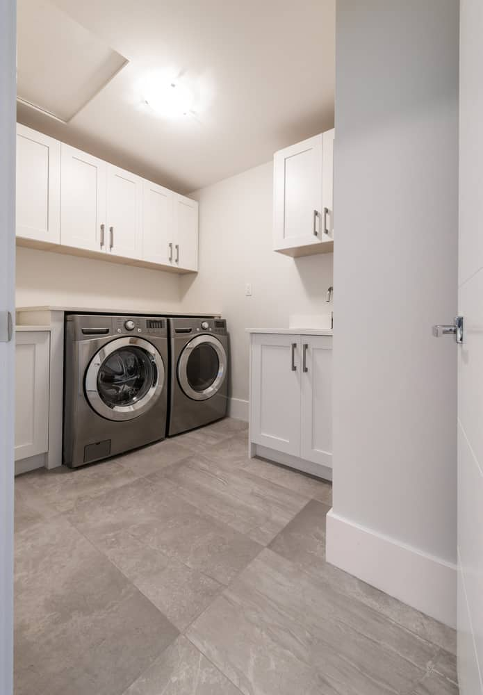 Spacious brand new laundry room in large home with white cabinets and stainless steel appliances on brown tile floor.
