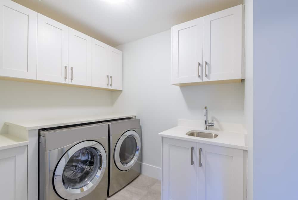Small but highly functional white laundry room with stainless steel appliances. Includes miniature sink.