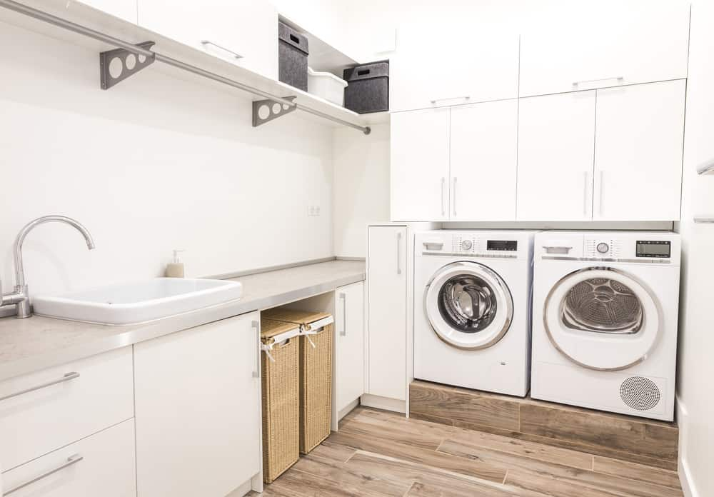 Very well planned out laundry room with hamper system, elevated washer and dryer placed beneath wall0mounted cabinets and a fabulous clothes drying rack.