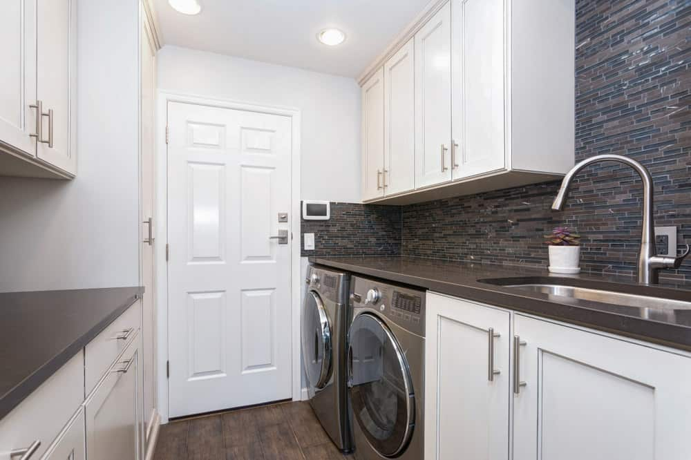 Stylish Contemporary Laundry Room With White Cabinets, Black Countertops  And Black Washing Machine And Dryer