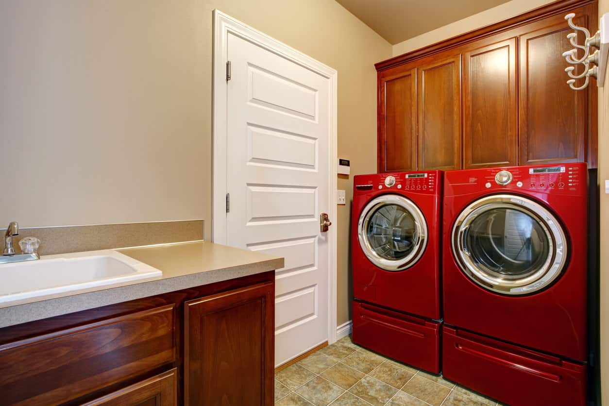 Mid-sized laundry room with rich red wood cabinery, white sink and red washing machine and dryer in a totally concealed separate laundry room space.