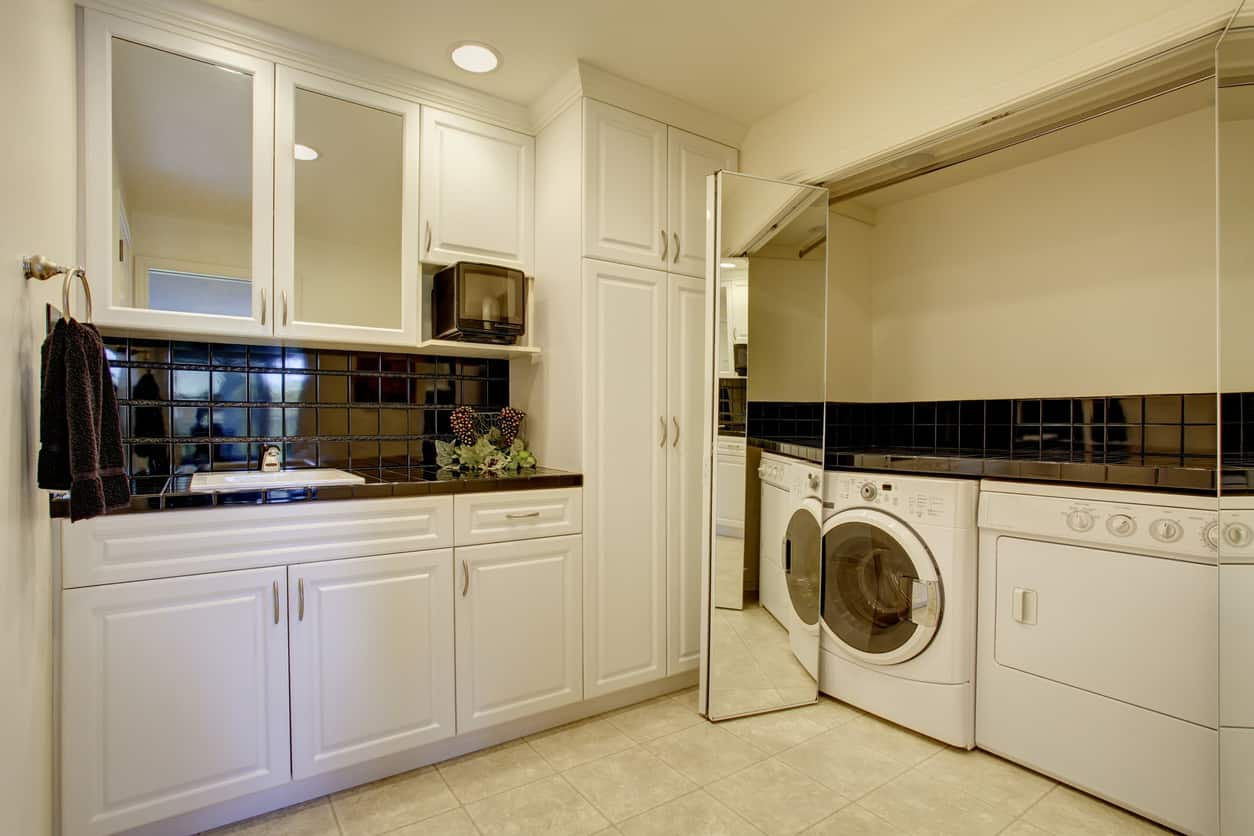 White and black laundry room with washing machine and dryer tucked into mirror-faced closet.