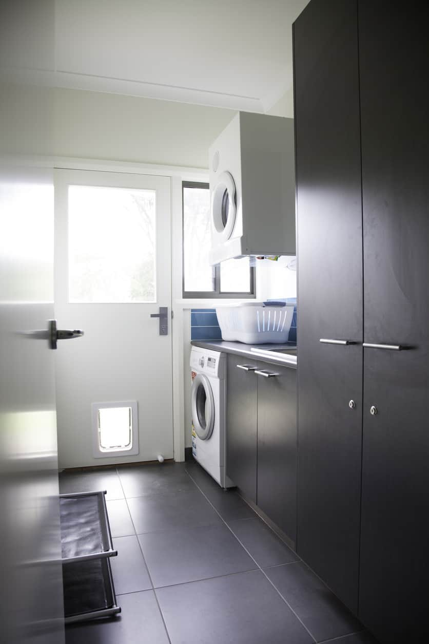 Modern dark gray and white small laundry room with wall-mounted dryer above washing machine.