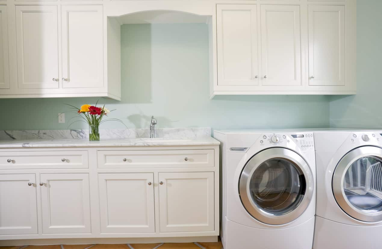 Close-up photo of white and light green laundry room with lots of custom white cabinetry set against a light green wall.