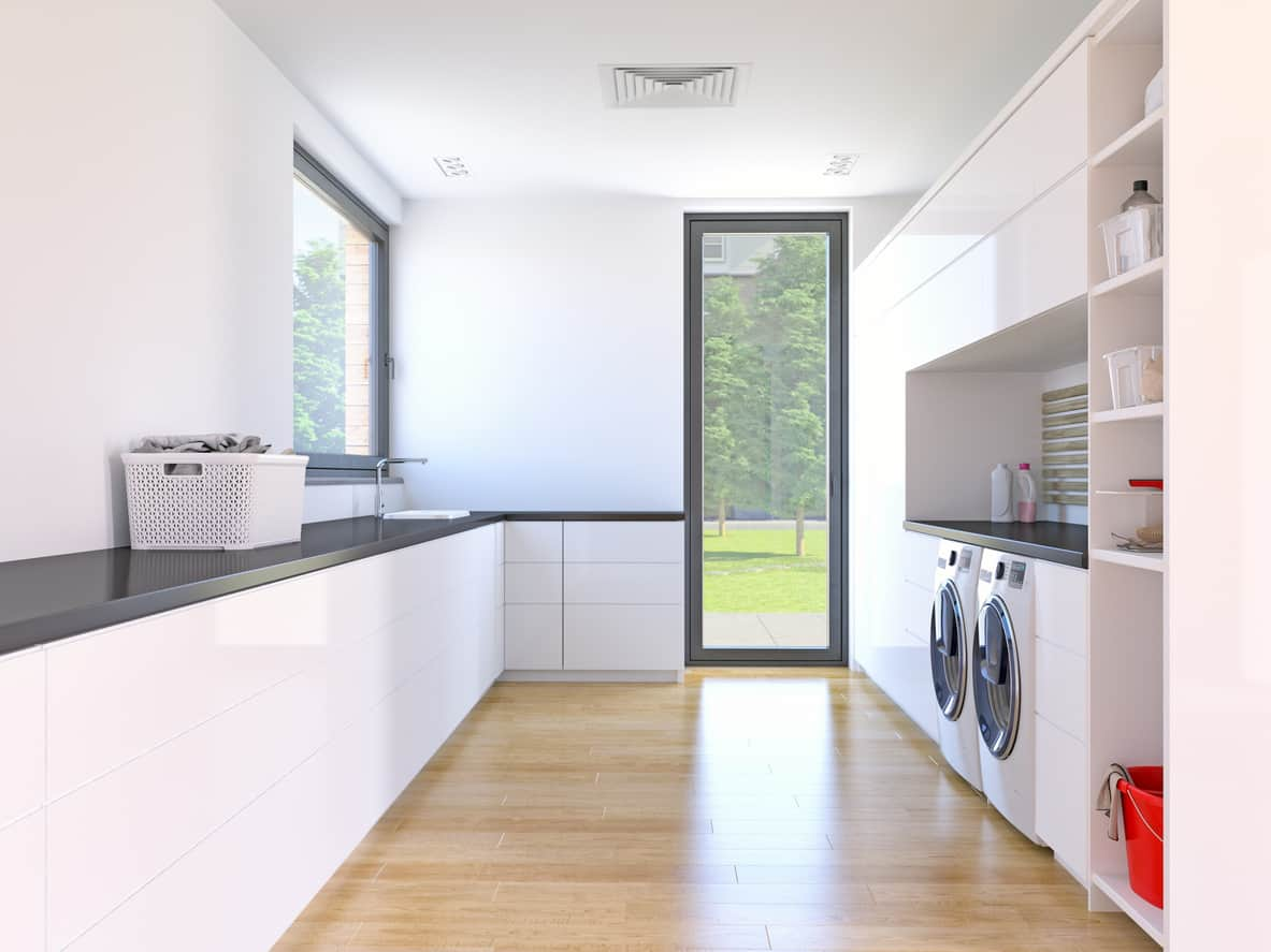 Sleek white and dark gray modern laundry room with light wood flooring and lots of natural light.