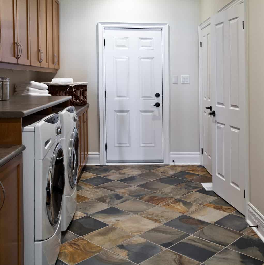 Separated laundry room with slate tile floor, dark wood cabinetry and light beige walls.