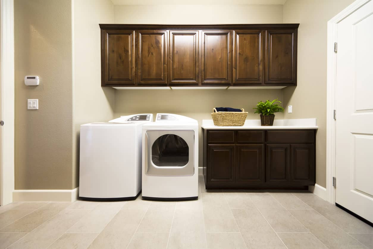 Non-cramped laundry room with wall-mounted cabinets, small counter and lots of floor space for organizing laundry workload.