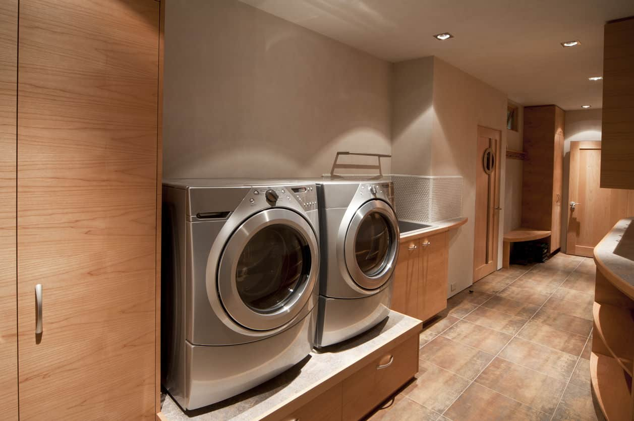 Huge custom designed and built laundry room that is about as perfect as it gets with sink, elevated appliances, plenty of cabinets, lots of floor space to organize clothing and so much more.