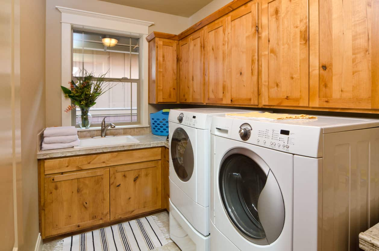 Craftsman cabinets fill this small laundry room with white laundry room appliances.
