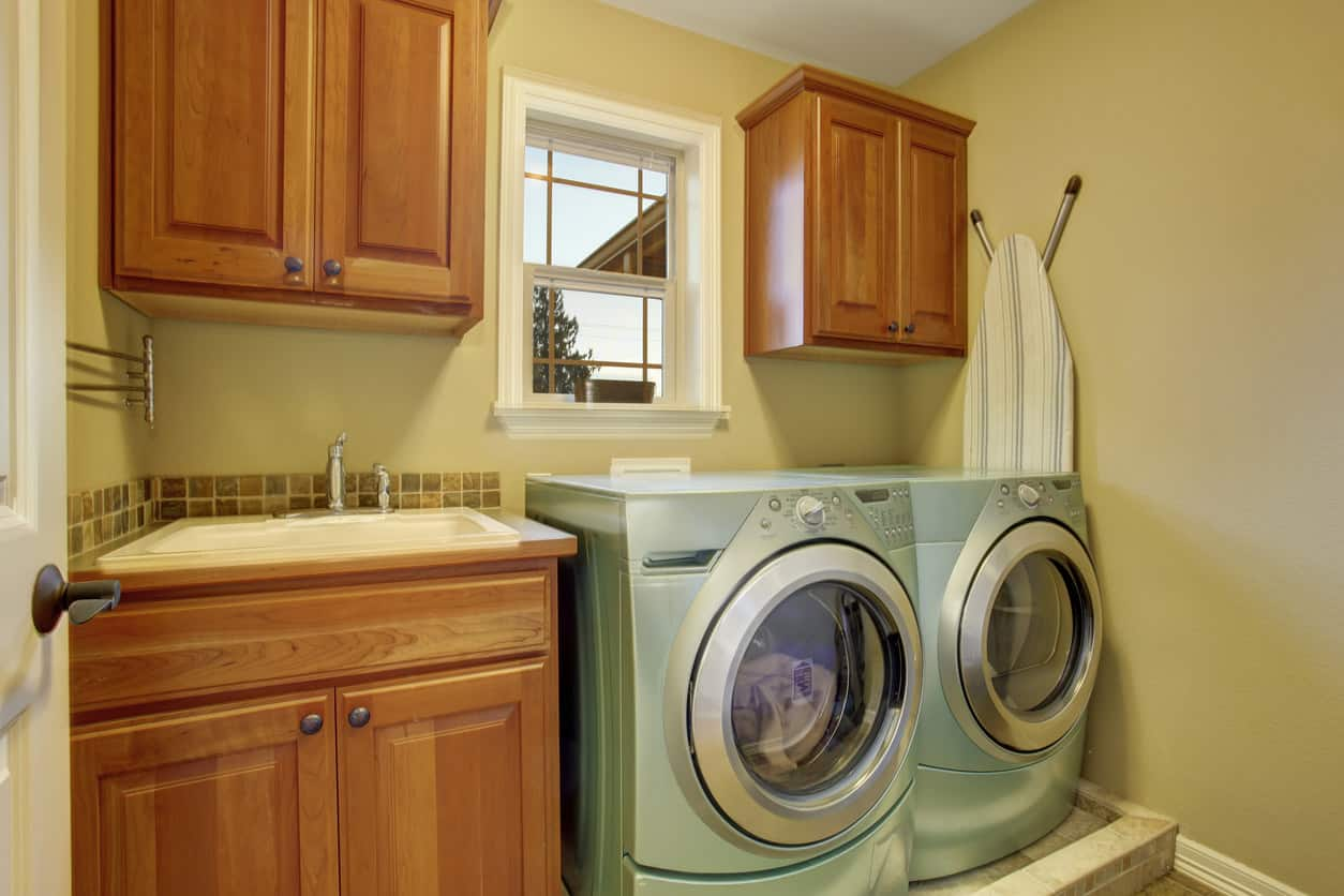 Small dedicated laundry room with washing machine and dryer elevated on small platform for more convenient access.