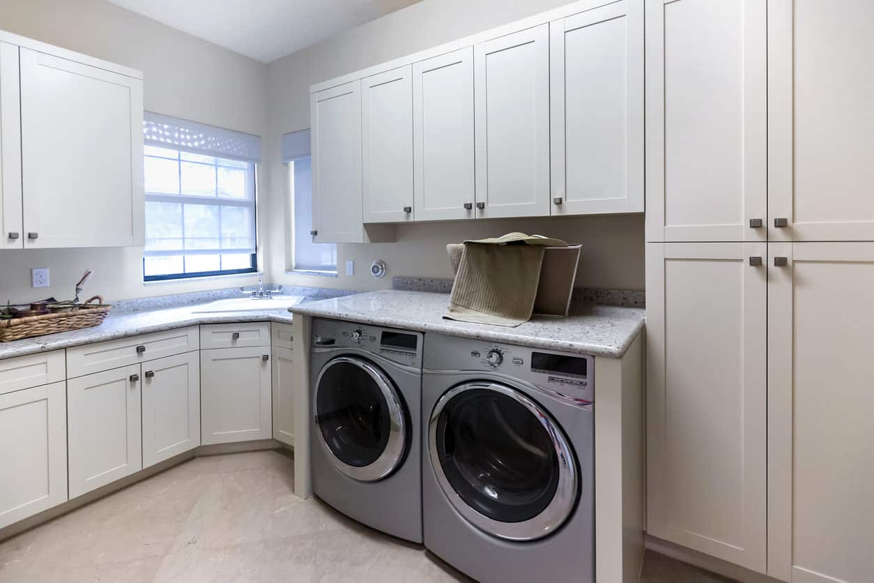 Traditional style large laundry room with custom built white cabinets, corner sink and stainless steel washer and dryer.