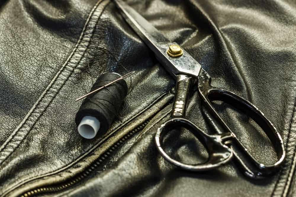 Leather shears and black thread and needle on top of a leather jacket.