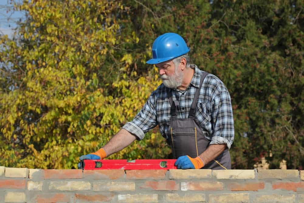 Workman using a level tool on top of the bricks.
