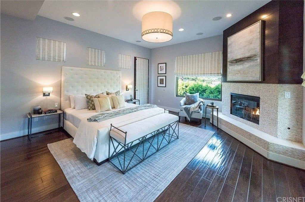 Large primary bedroom with rich, dark wood flooring, fireplace and area rug.