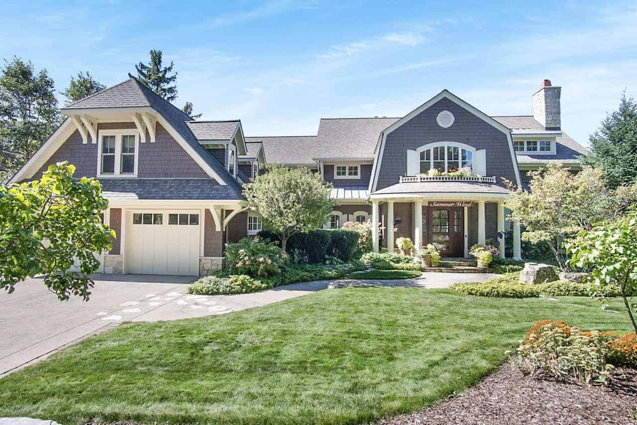 This large beach house boasts a sprawling yard with well-maintained lawn and healthy plants and trees.