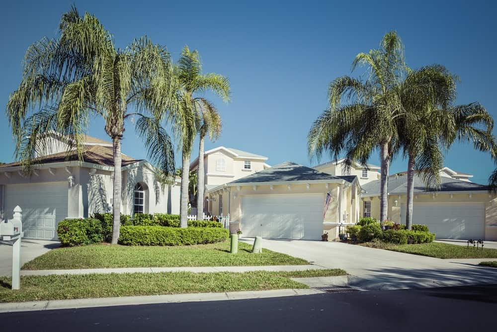 Luxurious white mansion with front lawn, one-door garage and asphalt driveway.