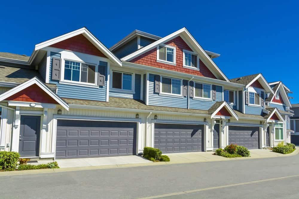 Luxurious multilevel townhouse with blue facade, three-door garage, and asphalt driveway.