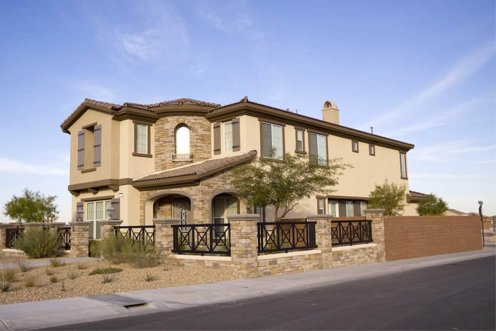 Large stucco house with stone brick decoration and enclosed fence made of traditional brick and stone brick with wrought iron railing.