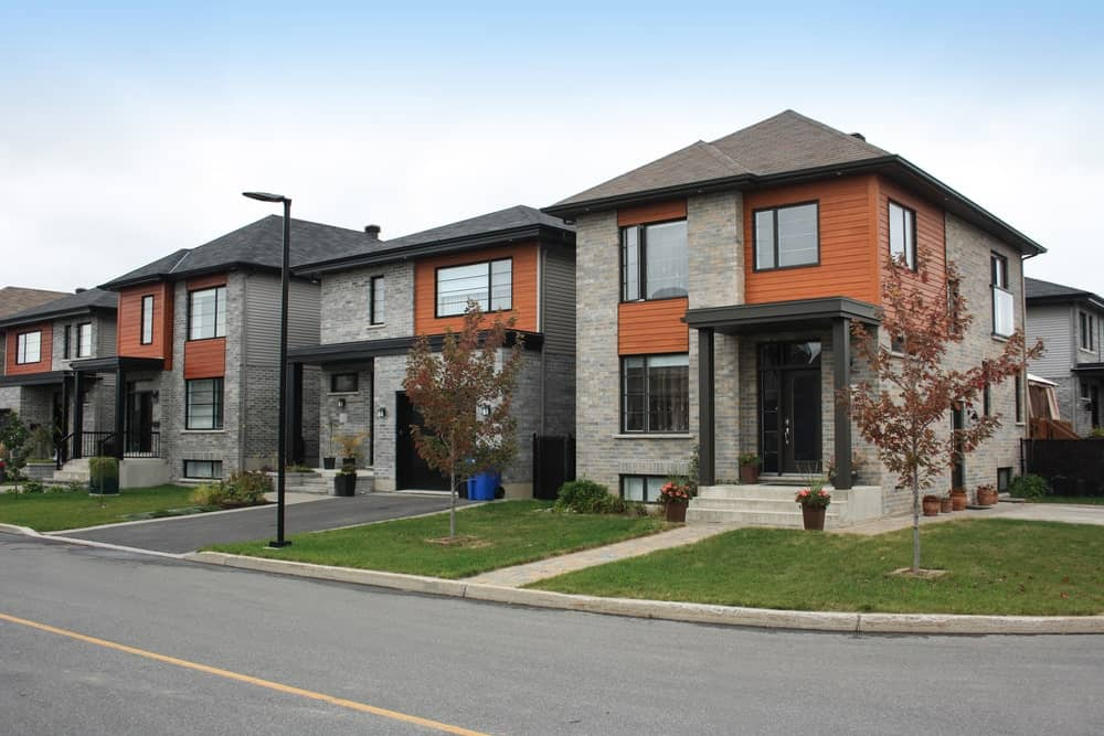 Luxurious apartments with gray facade, front grass patches, two-level interiors, and asphalt driveway.