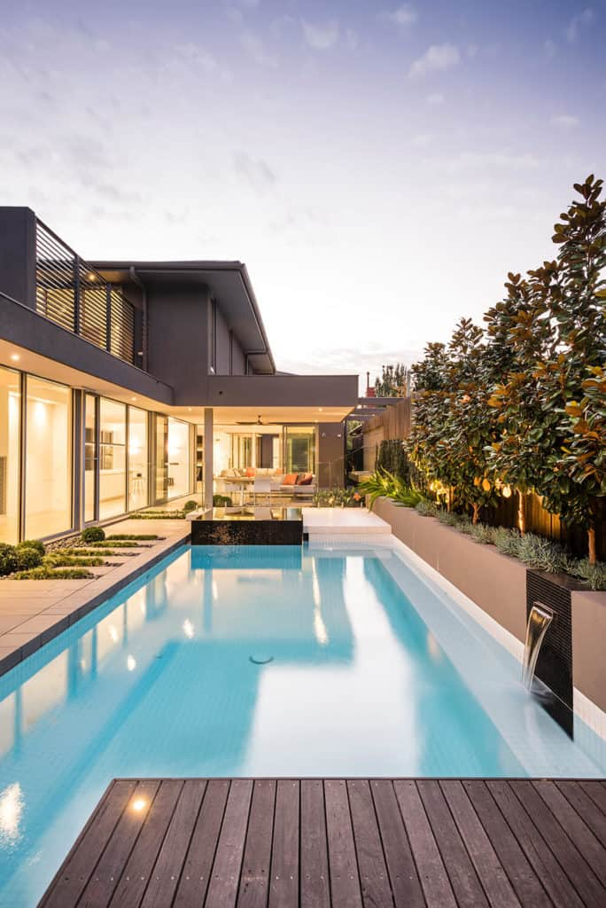 A modern gray house with a relaxing outdoor area featuring a swimming pool surrounded by plants and trees.
