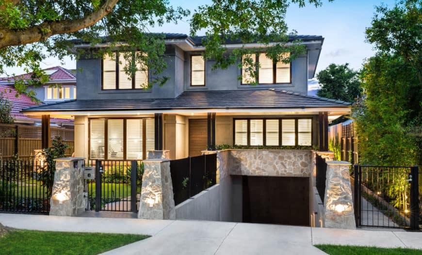 A contemporary gray house featuring a beautiful garden area.