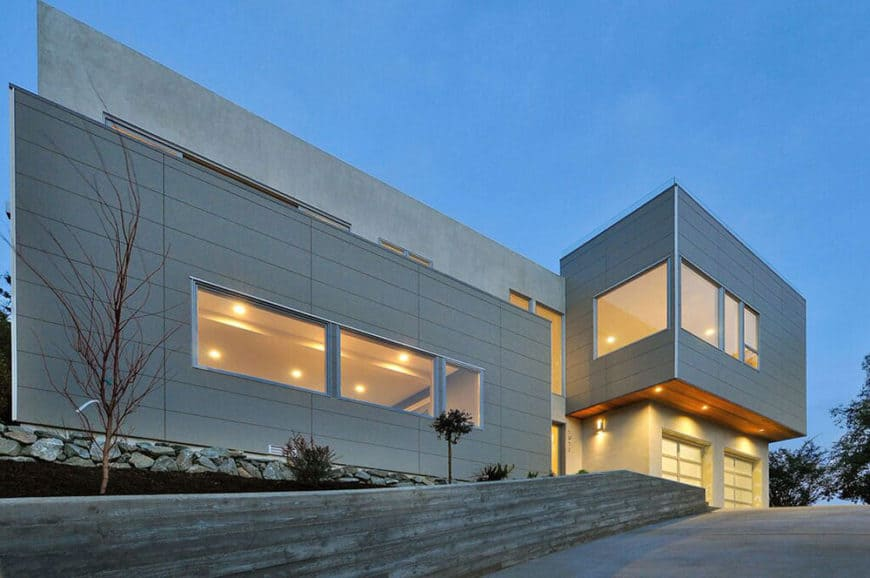 This large house features a gray exterior and a large driveway leading to the home's garage.