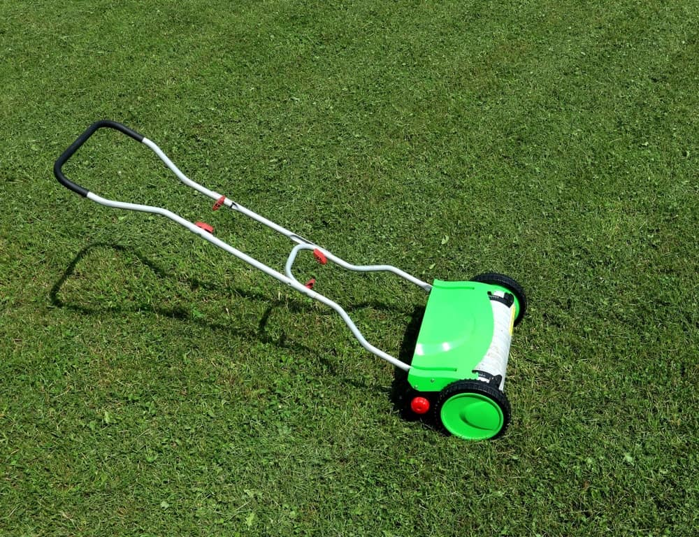 A manual mower is at rest on a lawn.