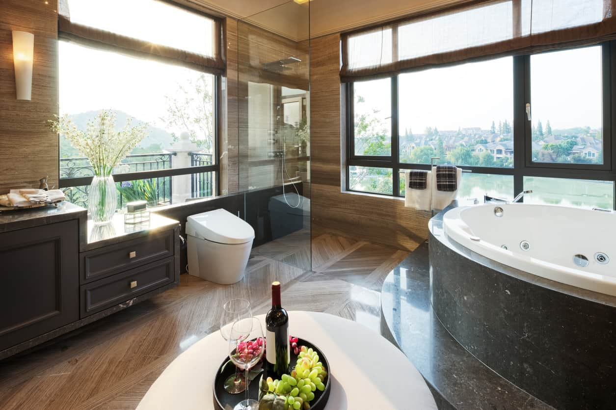 I'm not wild about this primary bathroom, but it's interesting given all the windows (which I love), but the open walk-in shower right next to the huge windows would make me nervous. Too much brown for my liking - needs white walls and ceiling.