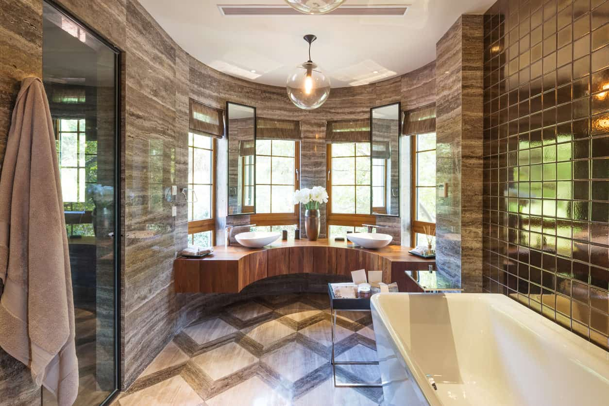 Luxurious primary bath with massive bay window area with curved floating wood vanity with two vessel basins. This bathroom would be so much better with white walls, don't you think?