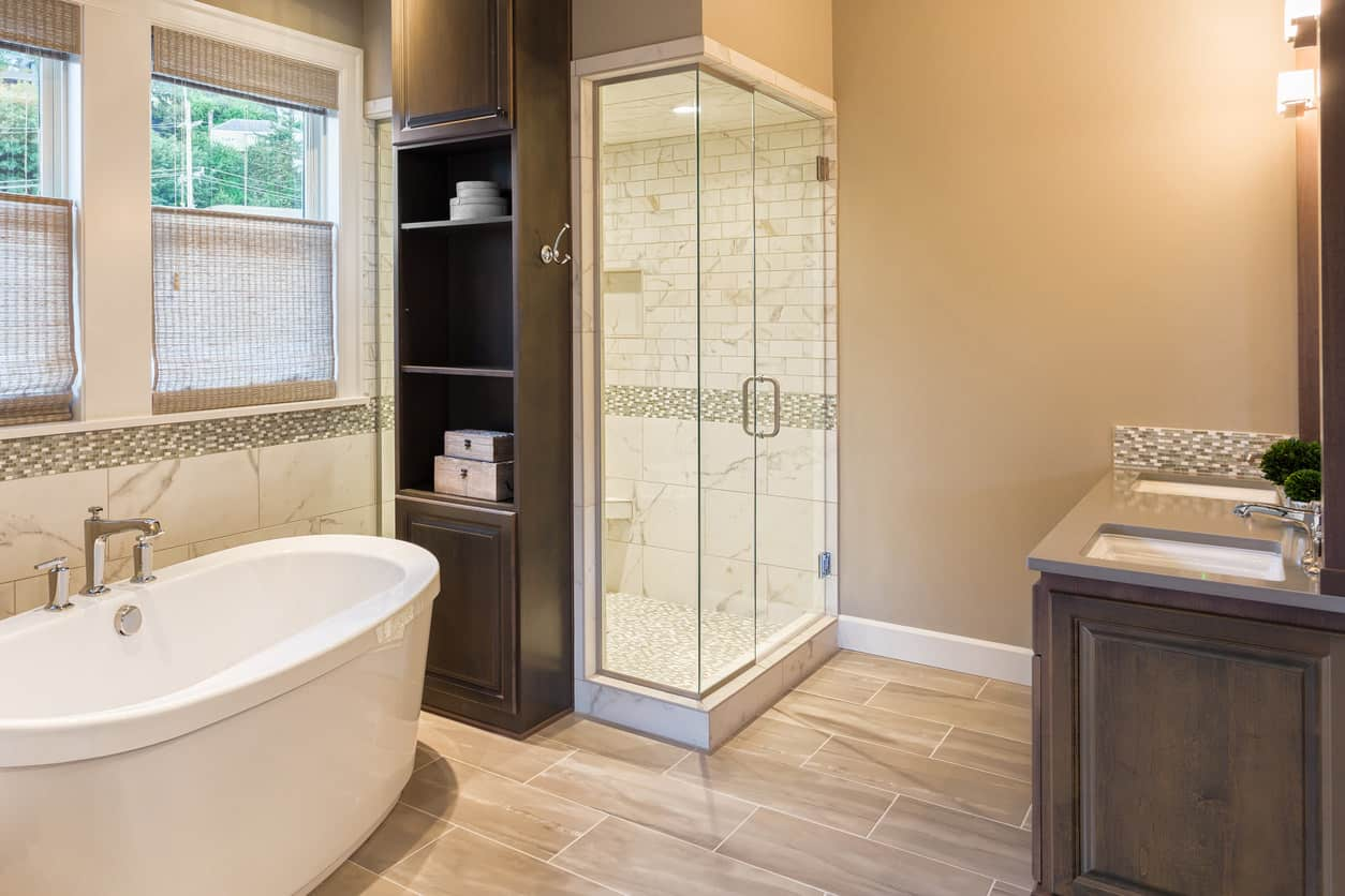 Spacious tan and white primary bathroom with dark wood vanity. I love the built in wood shelving next to the walk-in shower that is in arms-reach of the freestanding soaker tub.